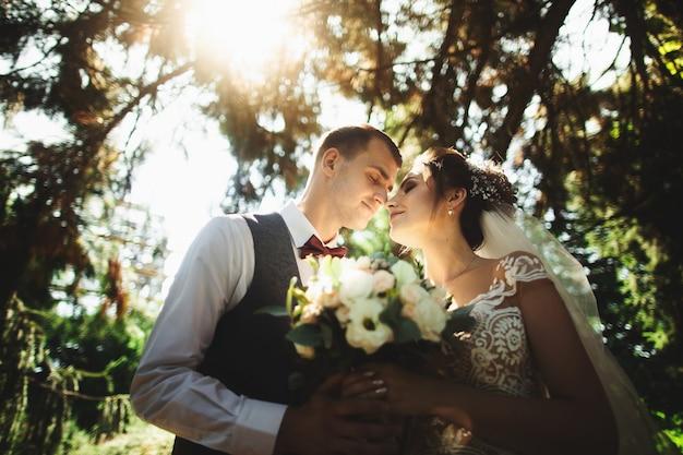 美しい晴れた日。自然の背景にポーズをとって結婚式のカップル