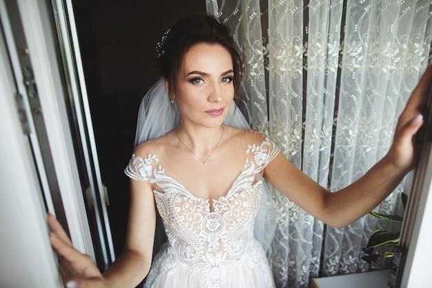 美しい花嫁スタイル。窓の近くの豪華なウェディングドレスに立つ結婚式の女の子