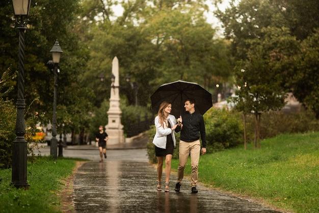雨の日に公園を歩いている若いカップル。ブダペストのラブストーリー