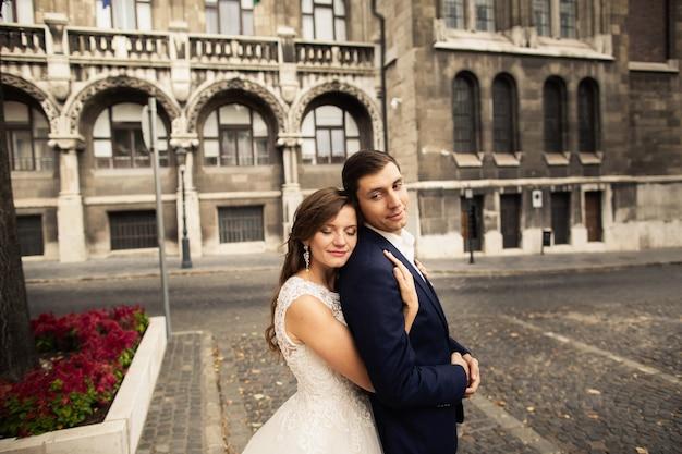 旧市街の通りで抱き締める新郎新婦。愛のカップルを結婚式。ブダペストでの除草