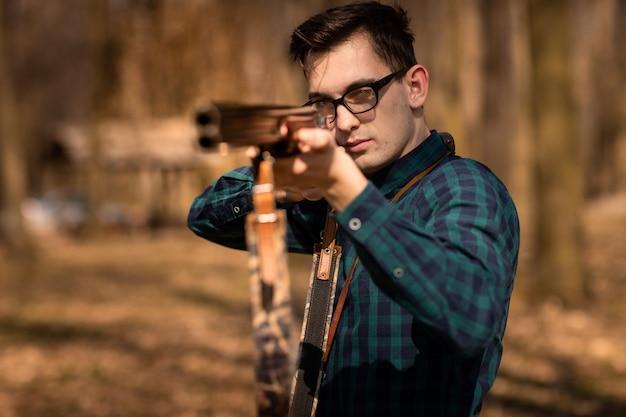 秋の狩猟シーズン。銃を持つ男ハンター。森の中で狩猟