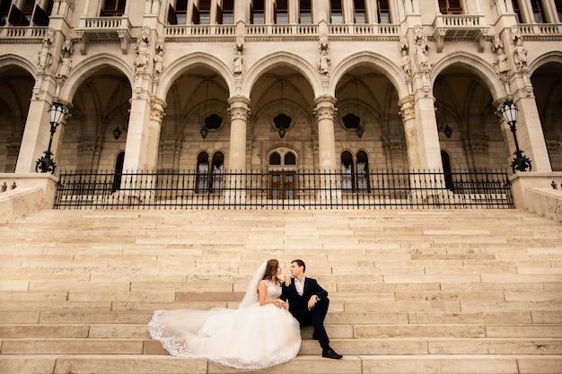 旧市街の通りで抱き締める新郎新婦。結婚式のカップルは、国会議事堂近くのブダペストで歩きます。