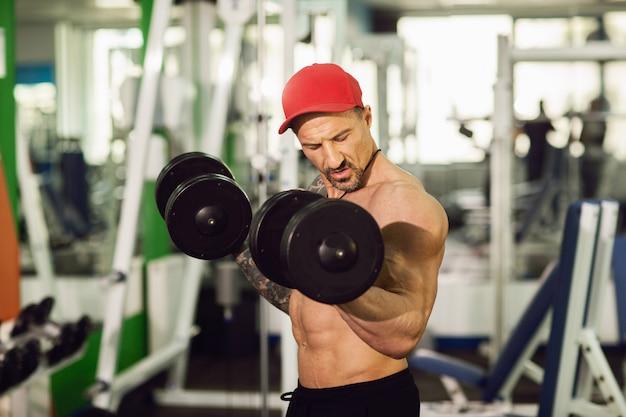 ジムで刺青のある男。カラフルなジムでダンベルを使って運動を実行する