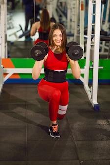 ジムでダンベルでのエクササイズの若い美しい女性。喜んで笑顔の女の子は彼女のトレーニングプロセスで楽しんでいます。