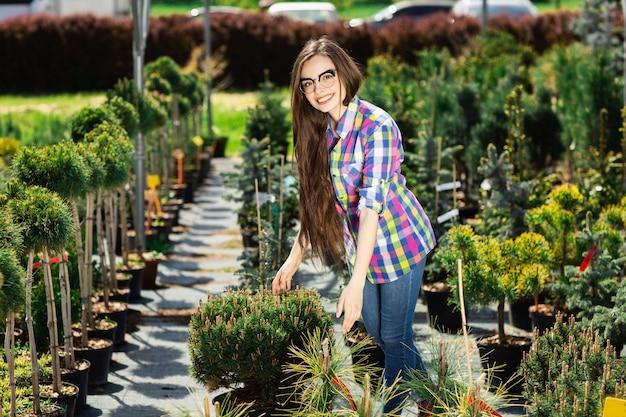きれいな女性を選択し、庭の緑の植物を購入します。