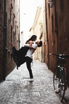 旧市街の狭い通りにいるカップルの官能的な写真。