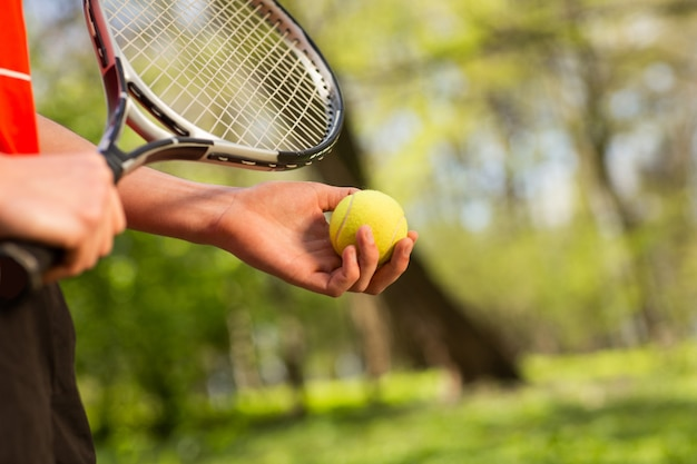 Крупным планом мужские руки держат теннисную ракетку и мяч на зеленом фоне.