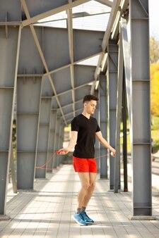 若い男が屋外で縄跳びでスキップします。運動とライフスタイル。