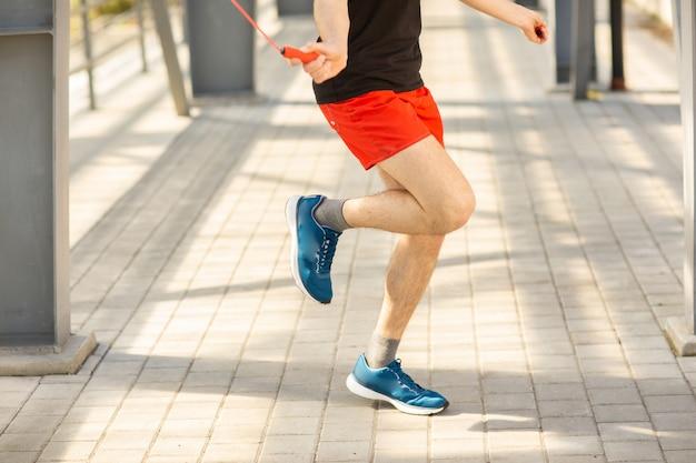 屋外で縄跳びでスキップする男性の足のクローズアップ。運動とライフスタイル。