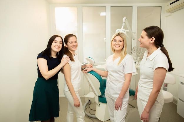 機器の近くでポーズをとる歯科医院の専門家のチーム