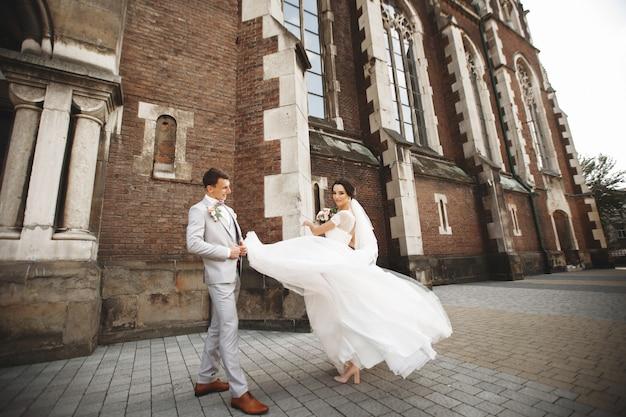 素晴らしい笑顔の結婚式のカップル。かなりの教会の近くのスタイリッシュな新郎新婦