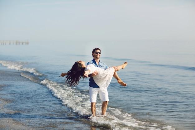 Счастливая пара гуляет и играет на пляже