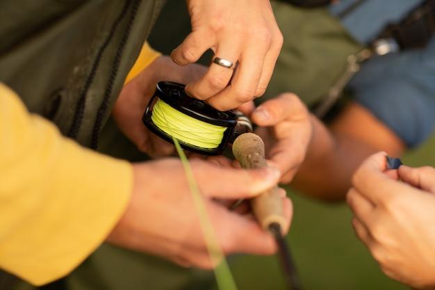釣りシーズン。紡績と漁師の手のクローズアップ