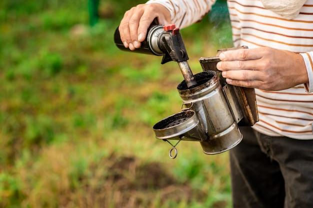 養蜂家は養蜂場の巣箱からミツバチを吸うための道具を準備します