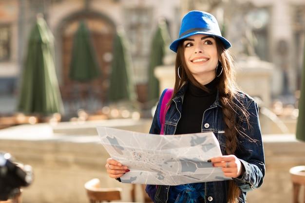 旧市街の通りを歩いてスタイリッシュな若い女性は、バックパックと青い帽子と一緒に旅行します。ウクライナ、リヴィウ