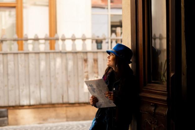 リヴィウの古い中庭を歩いて青い帽子の若い観光客