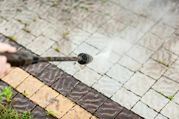 Крупным планом фото руки человека, чистит плитку травы в своем дворе. очистка под высоким давлением