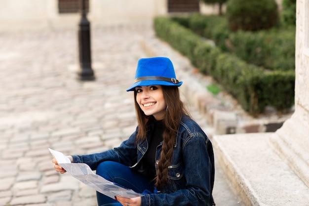 若い女性が古い中庭の階段に座り、地図を読みます。リヴィウ、ウクライナ