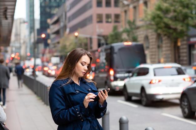 ビジネス会議のために、電話で場所を探しているビジネス女性。半分の長さの写真。
