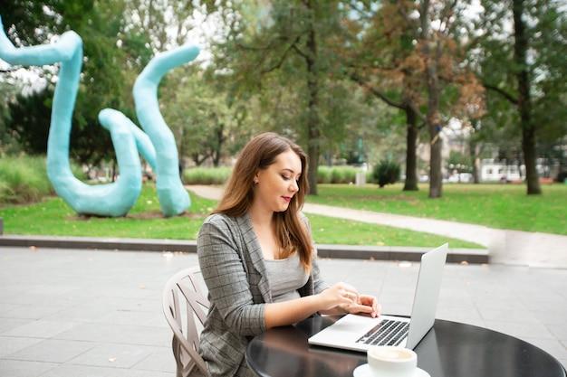 Бизнес женщина сидит в кафе на улице в городе, работает на ноутбуке.