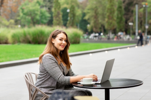 Бизнес женщина сидит в кафе на улице, работает на ноутбуке.