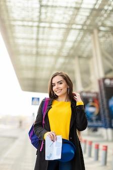 空港近くの通りで、地図を持って彼女の肩の後ろにバックパックを持つ美しい少女