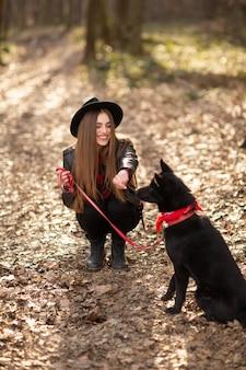 秋の公園を歩いて犬を持つ若い女の子