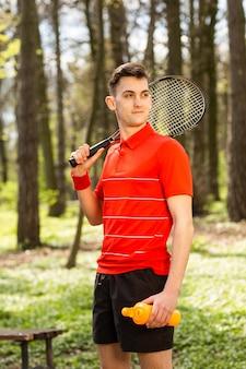 Человек представляют с теннисной ракеткой и оранжевой термопарой, на фоне зеленого парка. концепция спорта