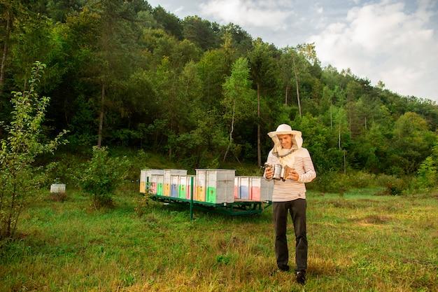 保護キャップの養蜂家は、養蜂場のハイブからミツバチを喫煙するためのツールを準備します。