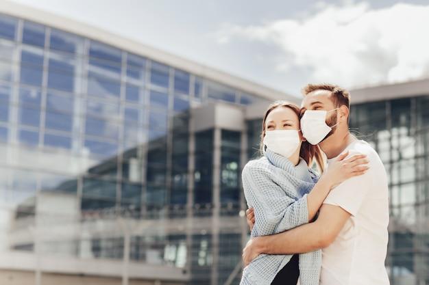 コロナウイルス検疫後の防護マスクの幸せな男と女の肖像画を閉じます。空港の近くの若いカップル、空の旅、旅行の概念を開く