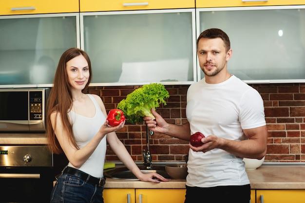 若いカップルはモダンなキッチンに立って、新鮮な果物や野菜の食品を準備しながらカメラ目線します。コショウ、サラダとリンゴを抱きかかえたを保持している女性。家族全員のための健康食品