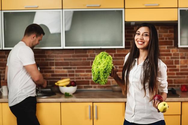 若いカップルが台所で料理。笑みを浮かべて、レタスとリンゴを保持している女性。背景の男。健康的な食事