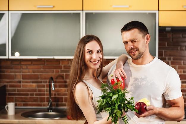 健康食品の広告。キッチンスタジオでポーズをとるかわいい若いカップルの肖像画を間近します。野菜と果物を手に持って、笑顔でカメラ目線の男女