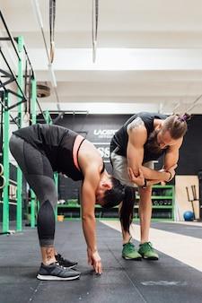 Молодой мужчина и женщина тренируются вместе