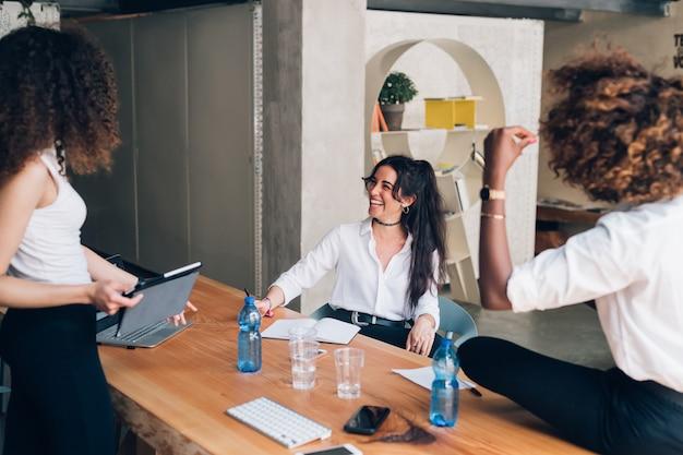 共同作業オフィスで会議を持つ若い多文化実業家