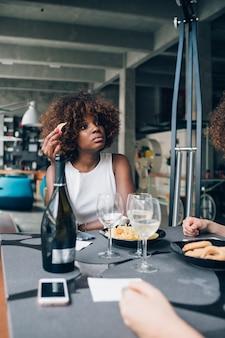 モダンなレストランの友達とワインを飲む若いアフリカ人女性