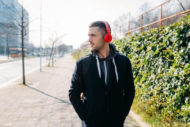 若い男が屋外で音楽を聴く