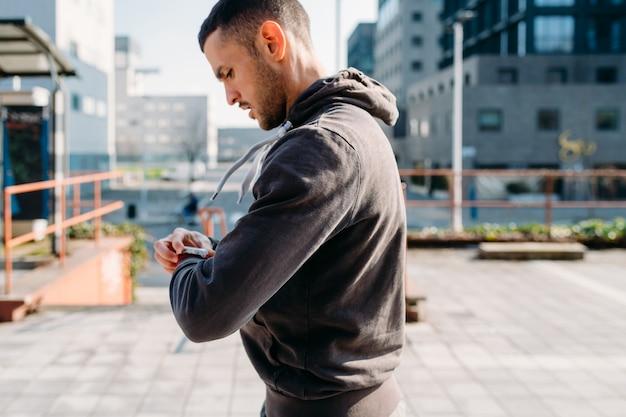 若い男がスマートウォッチを使用して屋外ストレッチ