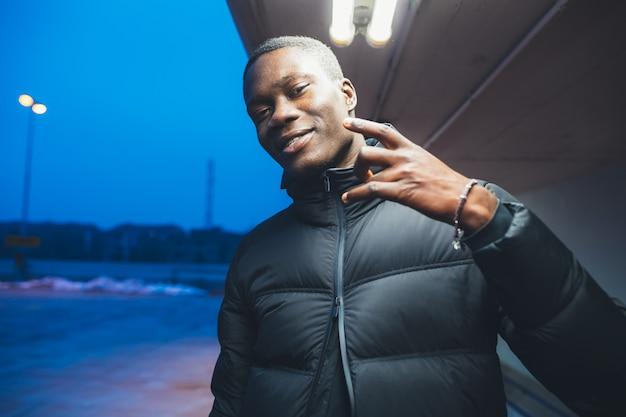 カメラを探している手で屋外ジェスチャーを立っている若い黒人男性の肖像画