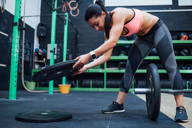 ダンベルトレーニングジムを準備する若い女性