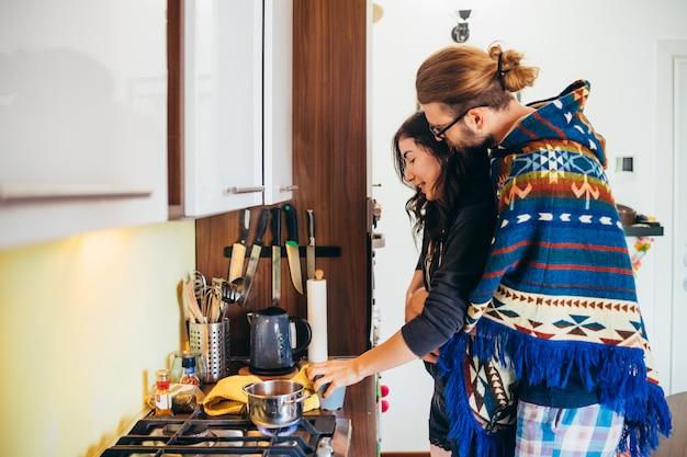 Ласковая молодая пара приготовления пищи в кухне дома
