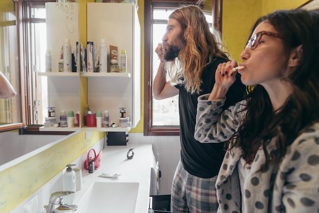 Молодая красивая пара дома утром чистить зубы ванной