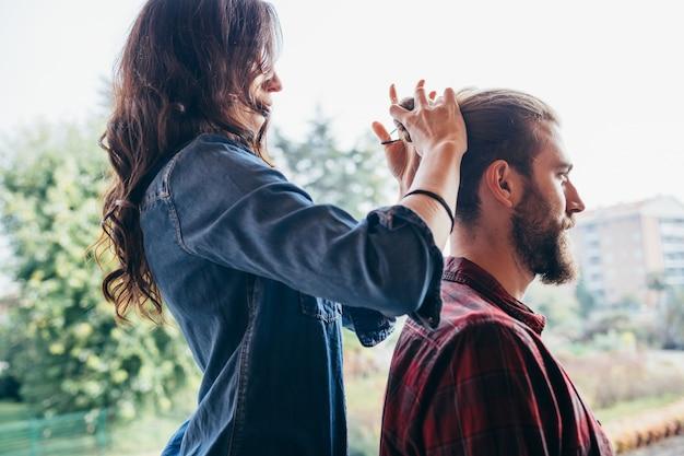 Молодая женщина, стоя на стуле, делает пучок волос для своего более высокого парня
