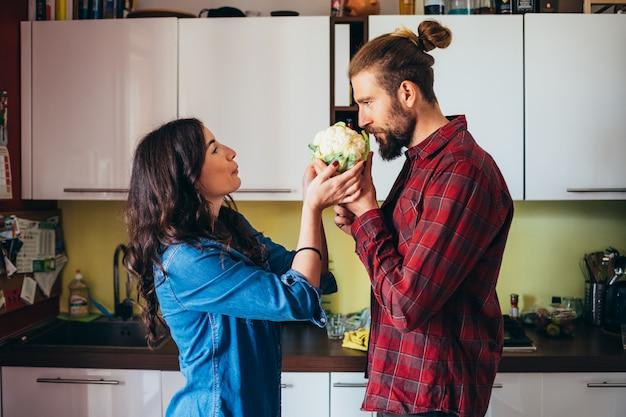 Ласковая молодая пара приготовления овощей в кухне дома