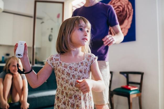 Девочка держит джойстик, играя в видеоигры у себя дома