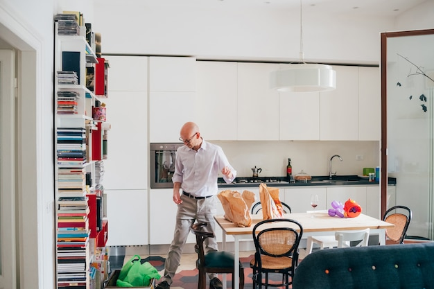 自宅で屋内の屋内成人男性が台所で食料品を開梱