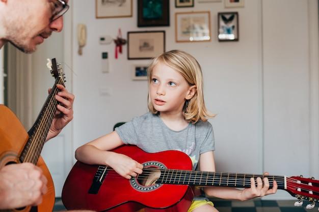 Отец учит свою дочь играть на гитаре