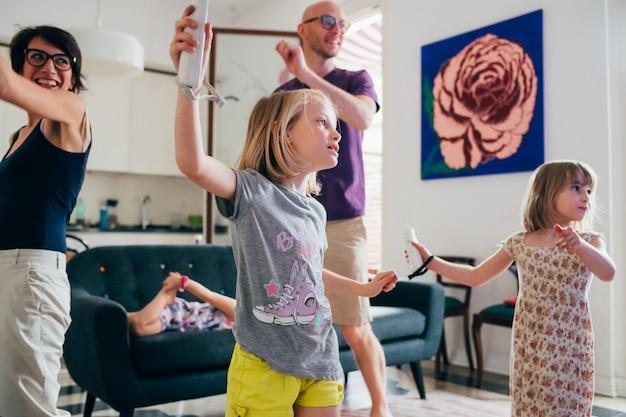 屋内でのビデオゲームで一緒に踊る家族