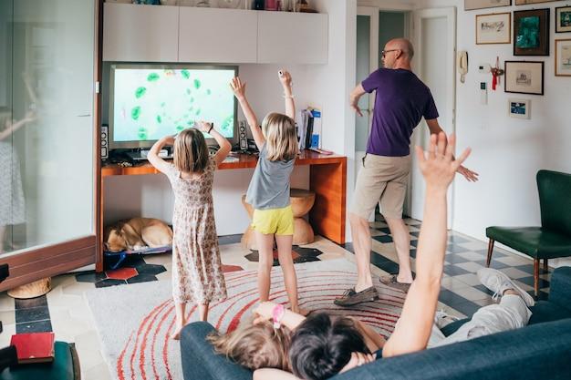 Семья танцует вместе в помещении, играя в видеоигры