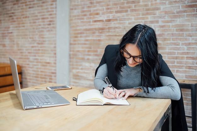 ワーキングデスクを座っているコンピューターを使用して屋内の若い美しい女性